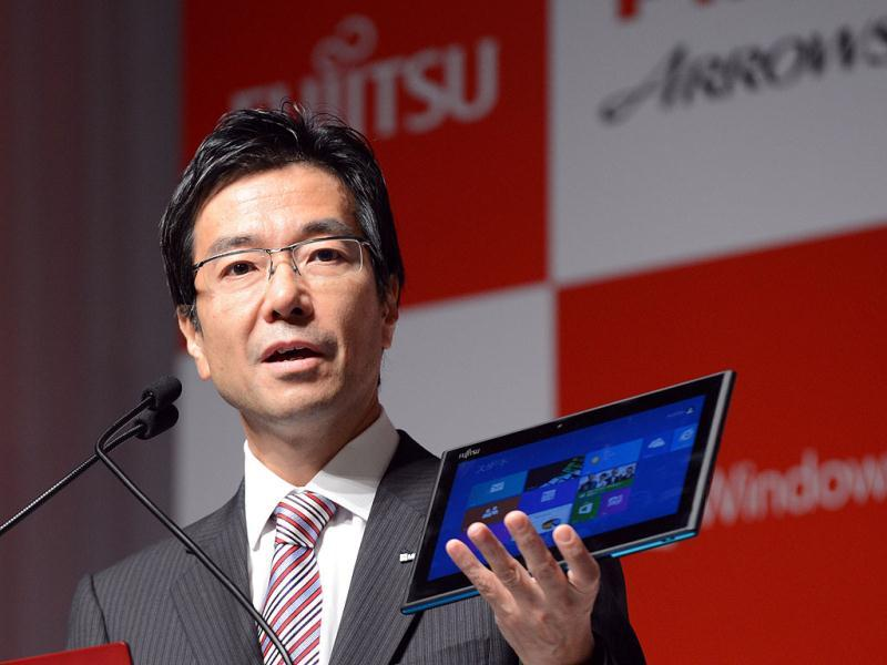 Microsoft Japan president Yasuyuki Higuchi displays Fujitsu's latest Windows 8 water-proof tablet PC,