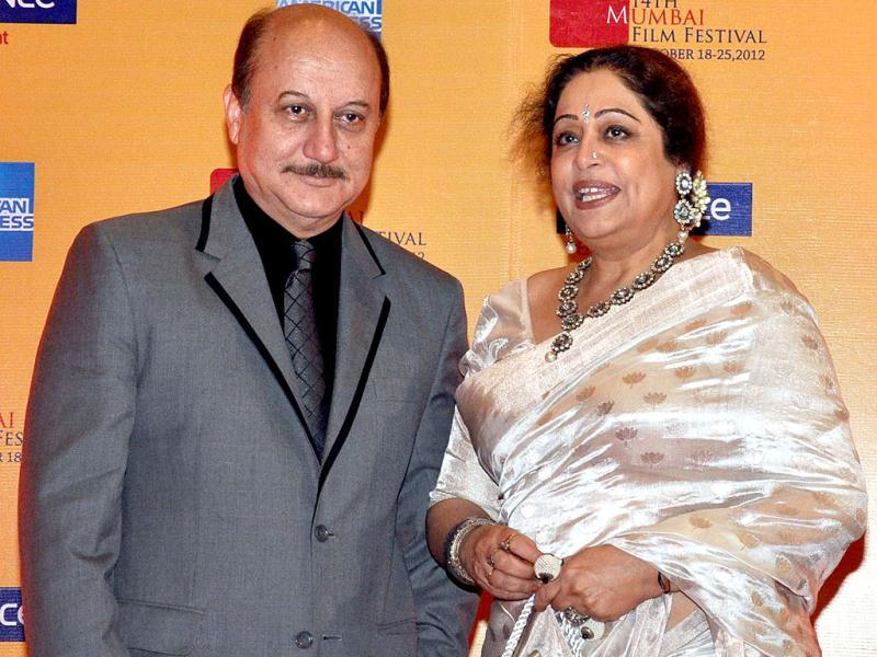 Bollywood actor Anupam Kher (L) poses with wife Kirron Kher pose as they attend the opening ceremony for the 14th Mumbai Film Festival in Mumbai. (AFP PHOTO)