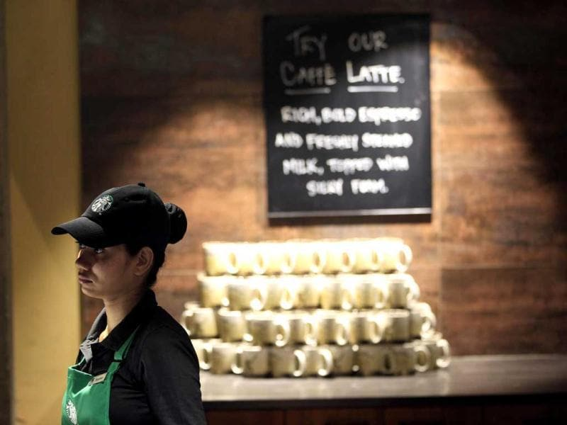 An employee of the newly inaugurated outlet of Starbucks stands at the store in Mumbai. Starbucks inaugurated its first store in India in a building in southern Mumbai as the Seattle-based coffee giant seeks growth in a market long associated with tea drinkers. AP/Rajanish Kakade