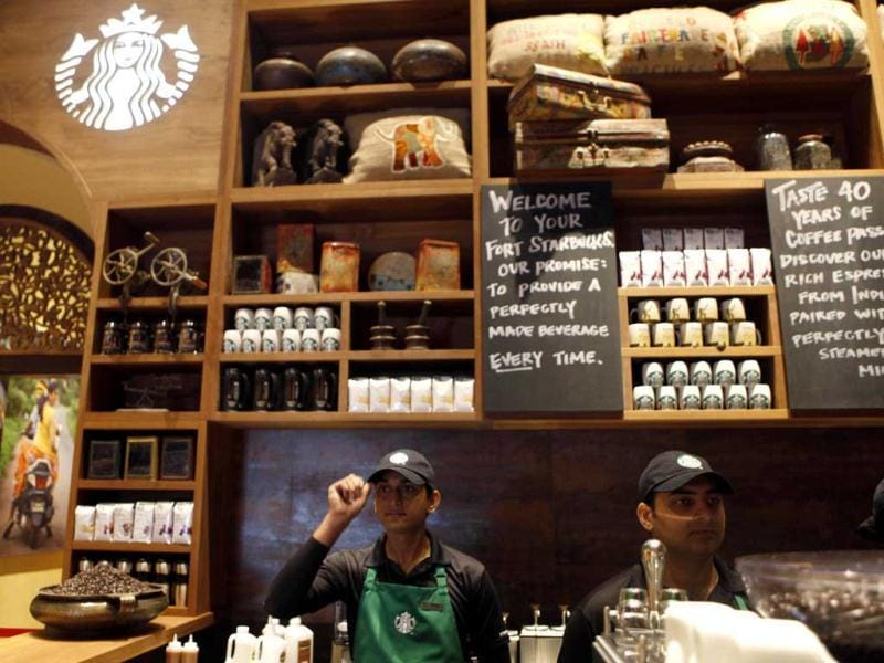 Employees of the newly inaugurated outlet of Starbucks work at a counter in Mumbai. Starbucks inaugurated its first store in India in a building in southern Mumbai. AP/Rajanish Kakade
