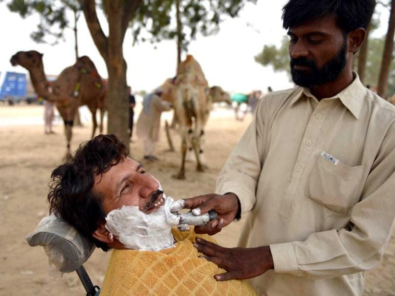 A barber shaves a customer beside camels at one of the main animal markets setup for the forthcoming Eid Al-Adha festival or the Feast of Sacrifice in Islamabad. AFP Photo