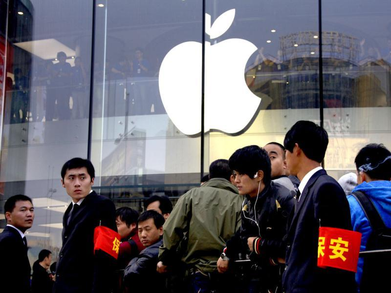 Security staff watch over a crowd gathered for the opening of a new Apple store in Beijing. Reuters/David Gray