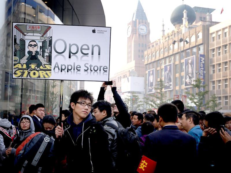 Crowd gather for the opening of a new Apple store holds a sign as he waits in line in Beijing. Reuters/David Gray