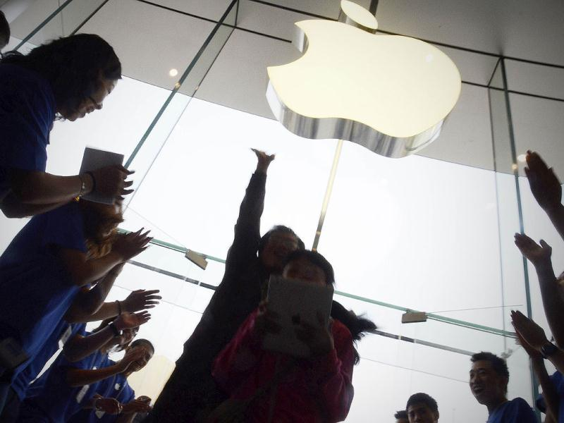Apple staff welcome customers in the new Apple store at WangFujin business district in Beijing. AFP/Wang Zhao