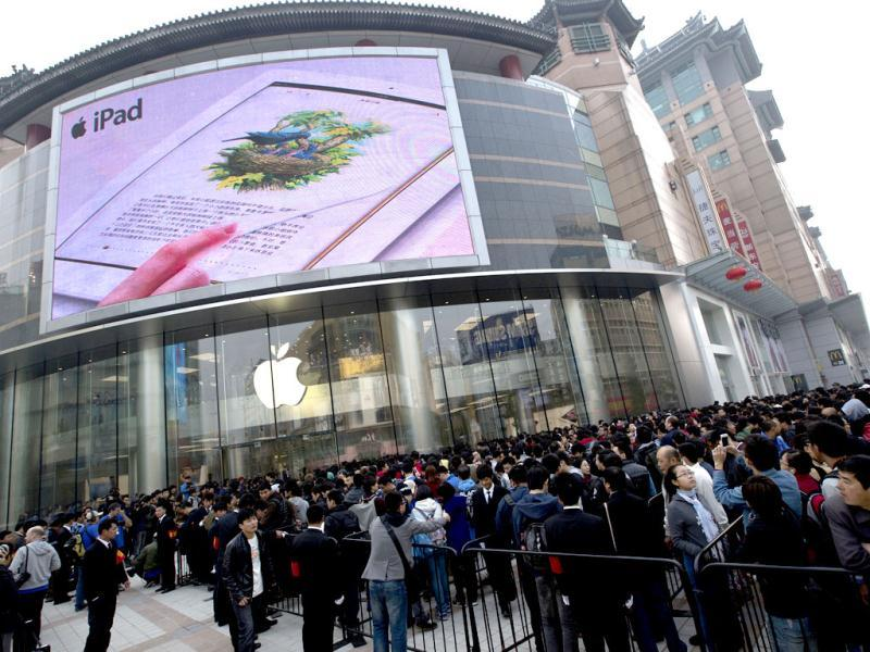 Chinese people line up outside a new Apple Store before it opens in Wangfujing shopping district in Beijing. AP/Andy Wong