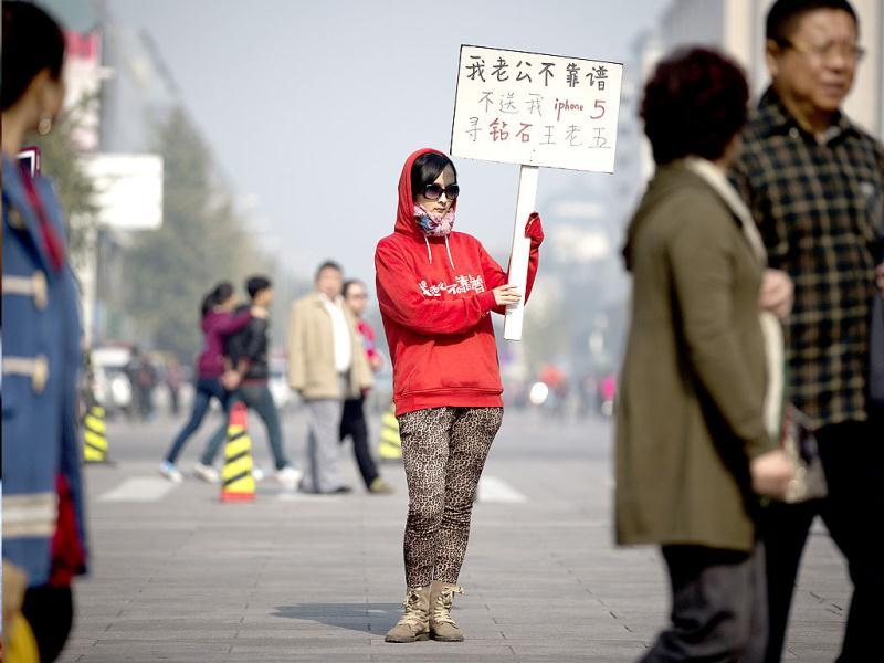 A woman holds a sign which reads