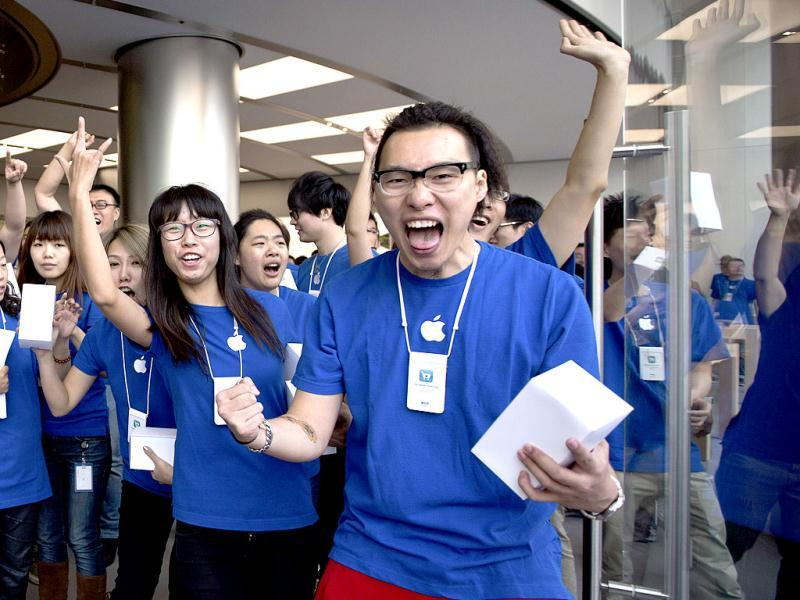Chinese employees cheer up at a new Apple Store during its official opening in Wangfujing shopping district in Beijing. AP/Andy Wong
