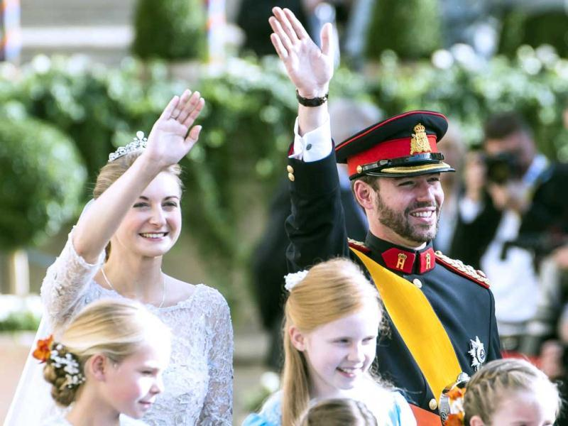 Princess Stephanie of Luxembourg and Prince Guillaume, hereditary Grand-Duke of Luxembourg wave to the crowd prior to leave the Notre-Dame cathedral of Luxembourg, after their religious marriage in Luxembourg. AFP Photo