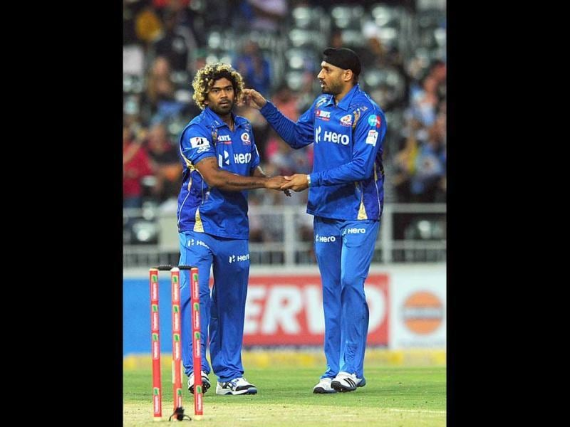 Mumbai Indians Harbhajan Singh (R) celebrates with his teammate Lasith Malinga for the wicket of Chennai Super Kings batsman Suresh Raina during the Champions League T20 (CLT20) game between Chennai Super Kings and Mumbai Indians at the Wanderers Stadium in Johannesburg. AFP Photo/Alexander Joe