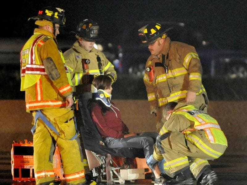 Rescue workers treat a person after they were removed from an airplane that crashed into the eastbound lanes of Interstate 94 north of Highway 11, near Racine Wis. The Skydive Midwest plane slid onto the interstate while attempting to land at the Sturtevant airport. (AP Photo/Journal Times, Gregory Shaver)