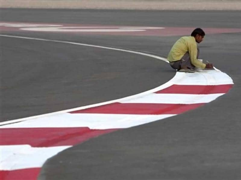 A worker paints the track of the Buddh International Circuit in preparation for the Indian Formula One Grand Prix in Noida, 38 kilometers (24 miles) from New Delhi. AP Photo/Tsering Topgyal