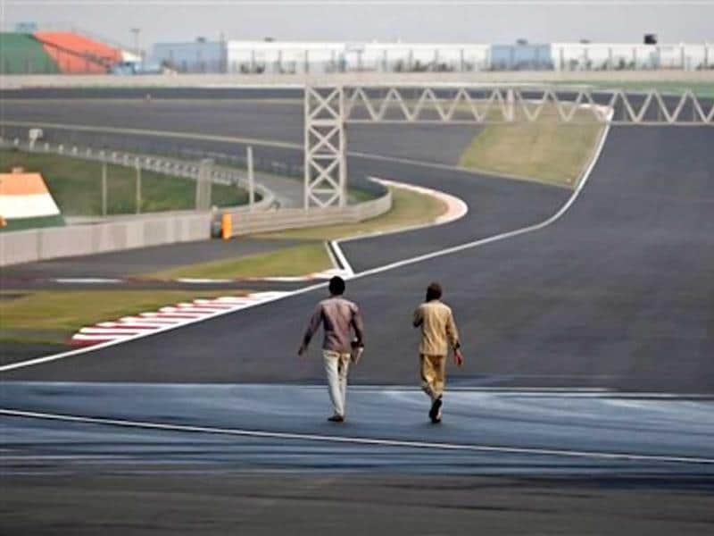 Workers walk at the Buddh International Circuit in Noida, 38 kilometers (24 miles) from New Delhi. AP Photo/Tsering Topgyal