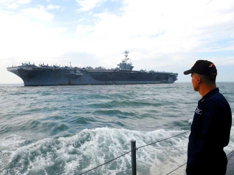 A Philippine Navy personnel looks at the nuclear-powered USS George Washington Nimitz-class aircraft carrier as it arrives in Manila. USS George Washington is in Manila for a short goodwill visit that aims to further enhance ties between the US and the Philippines through community relations projects and professional exchanges between the two countries. AFP PHOTO