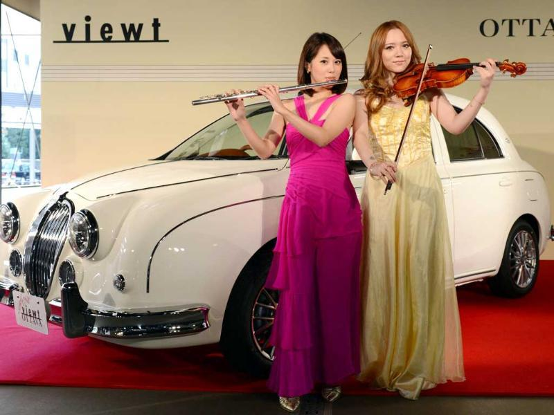 Japanese flutist Akiyo Ueta (L) and violinist Asuka Ochi (R) pose in front of Mitsuoka Motors' special edition 1200-cc classic sedan car, 'Viewt OTTAVA' during its press preview in Tokyo. AFP PHOTO