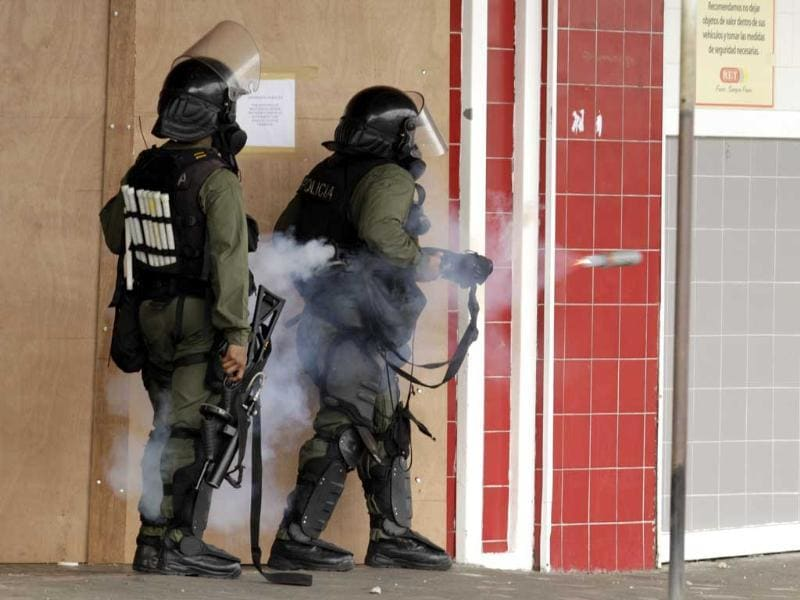 Police officers fire tear gas canisters against demonstratros during a protest in downtown Colon, Panama. Demonstrators protested over a new law allowing the sale of state-owned land in the duty-free zone next to the Panama Canal. AP Photo