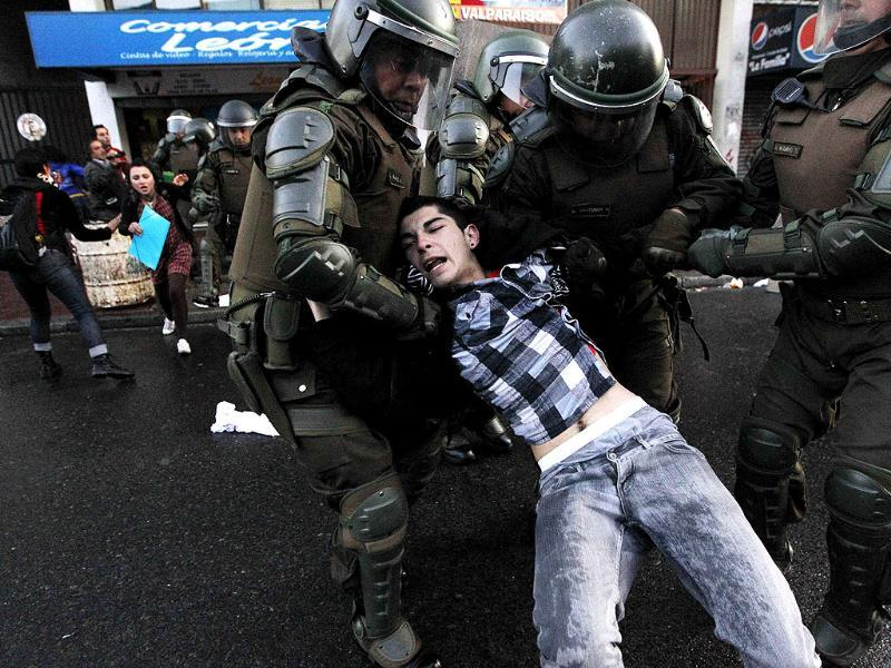 A Mapuche supporter is detained by riot police during a protest against the government in Valparaiso city, about 121 km (75 miles) northwest of Santiago. REUTERS