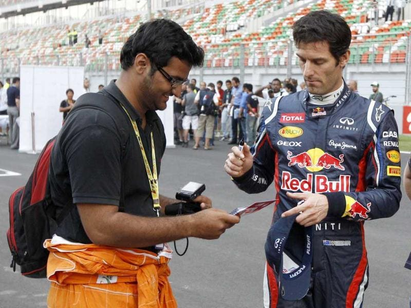Red Bull driver Mark Webber of Australia signs his autograph for a fan ahead of the Indian Formula One Grand Prix at the Buddh International Circuit in Greater Noida. AP Photo