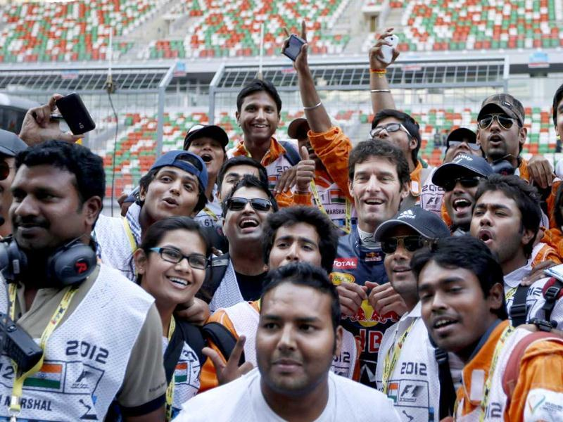 Red Bull driver Mark Webber, centre, of Australia poses for a photo with track marshals ahead of the Indian Formula One Grand Prix at the Buddh International Circuit in Greater Noida. AP Photo