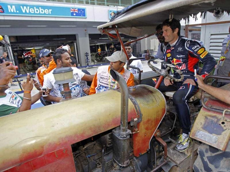 Red Bull Formula One driver Mark Webber of Australia sits in a tractor in the pit lane at the Buddh International Circuit in Greater Noida. Reuters Photo