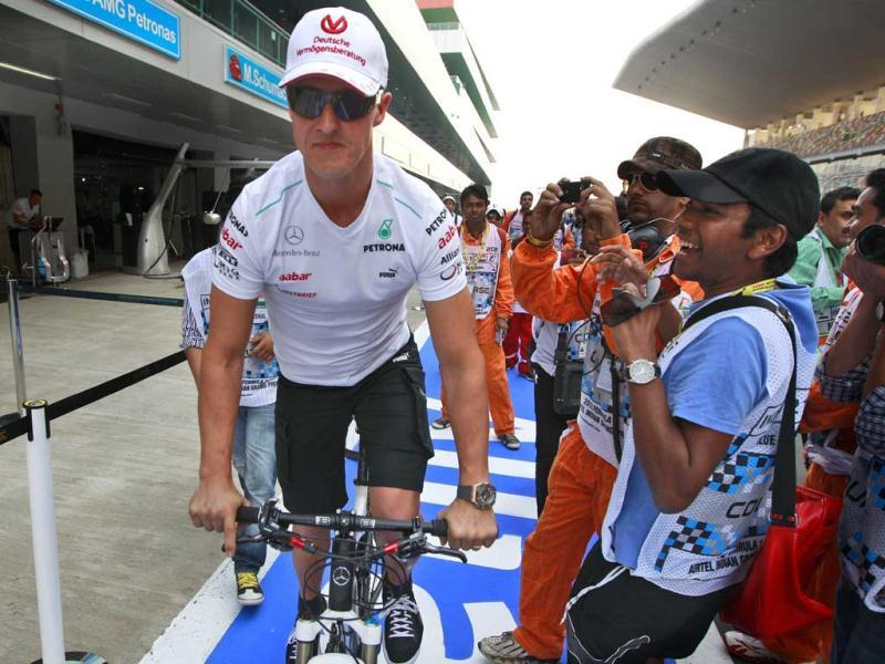 Mercedes driver Michael Schumacher of Germany rides his bike down pit lane ahead of the Indian Formula One Grand Prix at the Buddh International Circuit in Greater Noida. AP Photo