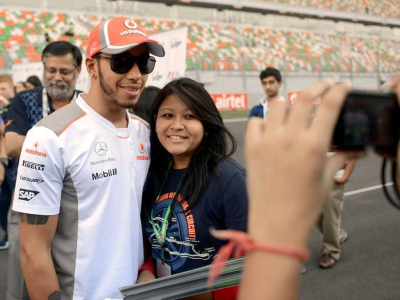 McLaren Mercedes driver Lewis Hamilton (2L) of Britain poses with a fan at The Buddh International circuit in Greater Noida. AFP Photo