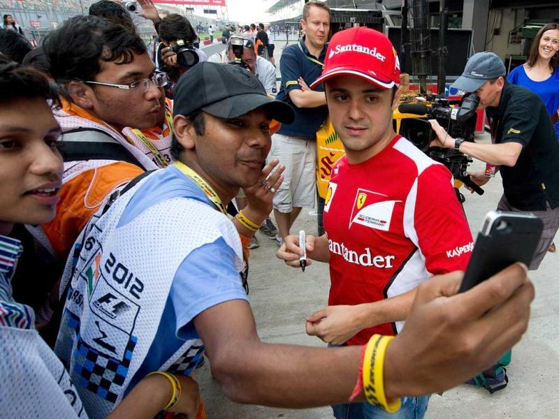 Ferrari driver Felipe Massa (R) of Brazil has his picture taken with fans at The Buddh International circuit in Greater Noida. AFP Photo