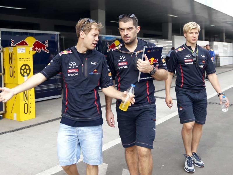Red Bull driver Sebastian Vettel of Germany, left, walks with team members at the Buddh International Circuit ahead of the Indian Formula One Grand Prix in Greater Noida. AP Photo