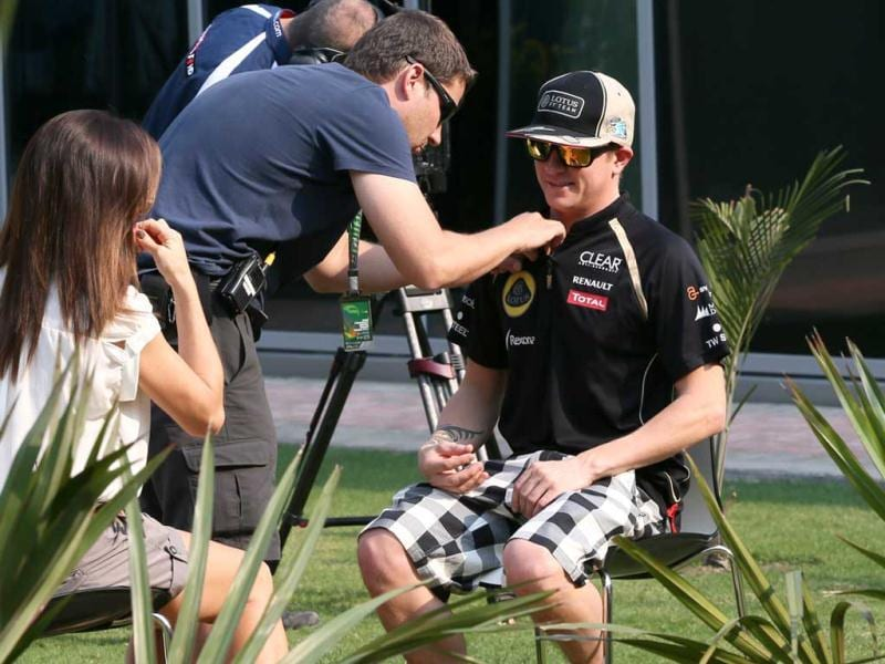 Lotus driver Kimi Raikkonen, right, of Finland prepares for a television interview in the F1 paddock ahead of the Indian Formula One Grand Prix at the Buddh International Circuit in Greater Noida. AP Photo