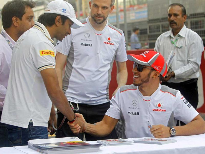 McLaren Formula One driver Lewis Hamilton of Britain (R) shakes hands with HRT Formula One driver Narain Karthikeyan of India at the Buddh International Circuit in Greater Noida, on the outskirts of Delhi. Reuters Photo