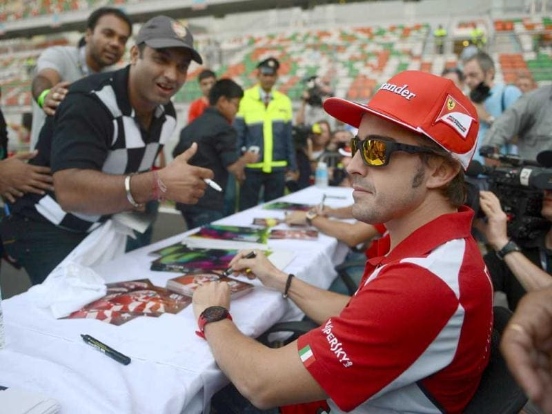 Ferrari driver Fernando Alonso (R) of Spain poses for a fans during an autograph session at The Buddh International circuit in Greater Noida. AFP Photo