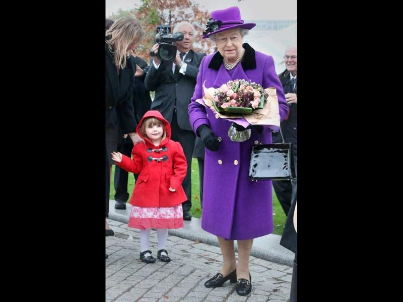 Bethany Wiles aged three-years-old looks up at Britain's Queen Elizabeth II at the opening of the recently re-built Jubilee Gardens in London. AP Photo/Peter Macdiarmid