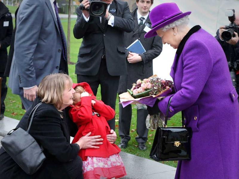 Bethany Wiles, aged three, covers her face and is held by her mother Rae Wiles after giving flowers to Britain's Queen Elizabeth at a ceremony at Jubilee Gardens in London. Reuters/Peter Macdiarmid