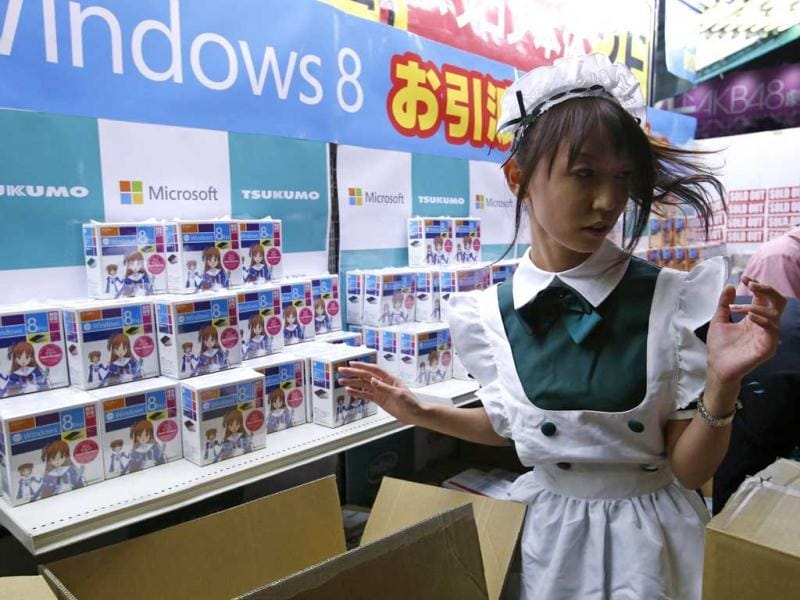 A shop staff dressed as a maid works next to Microsoft Corp's Windows 8 operating system packaged in boxes with anime design, as Windows 8 goes on sale outside an electronics store at the Akihabara district in Tokyo.Reuters/Toru Hanai