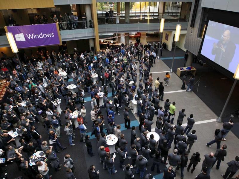 Employees look on as Microsoft CEO Steve Ballmer speaks via a webcast during an event unveiling a new Microsoft Windows operating system at the company's headquarters in Redmond, Washington. (AP Photo/Elaine Thompson)