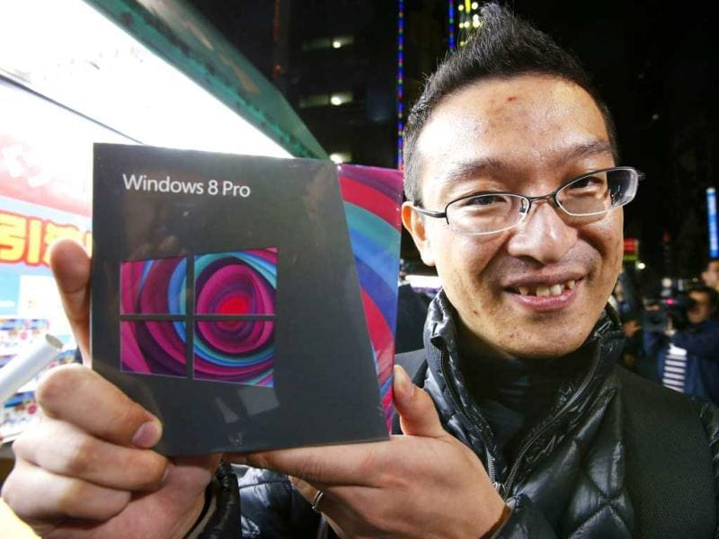 Takatoshi Kojima poses with his Microsoft Corp's Windows 8 operating system outside an electronics store at the Akihabara district in Tokyo. Reuters/Toru Hanai