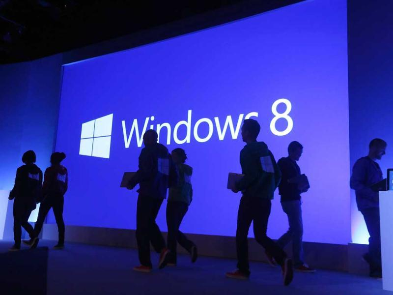 People walk past a display at a press conference unveiling the Microsoft Windows 8 operating system in New York City. AFP photo