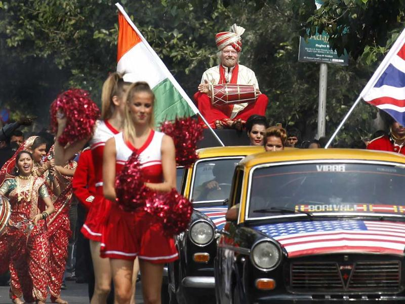 Virgin Group's Sir Richard Branson sitting on top of a black-and-yellow city taxi, plays a traditional drum during a photo opportunity parade in Nariman point. Branson is in the city to announce the launch of Virgin Atlantic's new service from Mumbai to London. HT Photo/Vijayanand Gupta