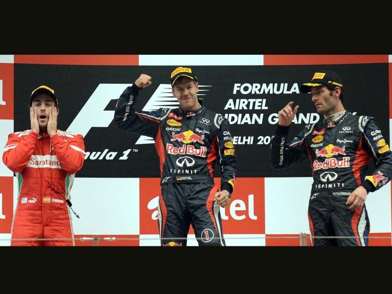 Winner Red Bull-Renault driver Sebastian Vettel of Germany (C) celebrates at the podium as second-placed Ferrari driver Fernando Alonso of Spain (L) and third-placed Red Bull-Renault driver Mark Webber of Australia watch after victory at the Formula One Indian Grand Prix at The Buddh International circuit in Greater Noida . AFP Photo