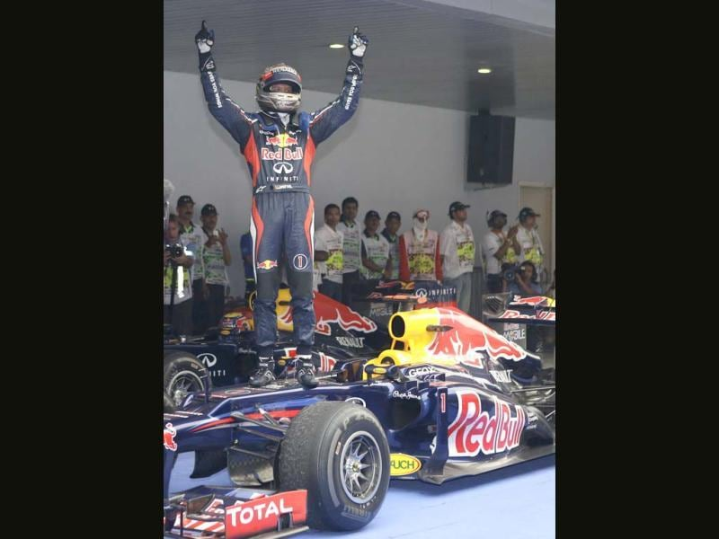 Red Bull driver Sebastian Vettel of Germany stands on his car as he celebrates his win at the Indian Formula One Grand Prix at the Buddh International Circuit in Noida. (AP Photo/Mark Baker)
