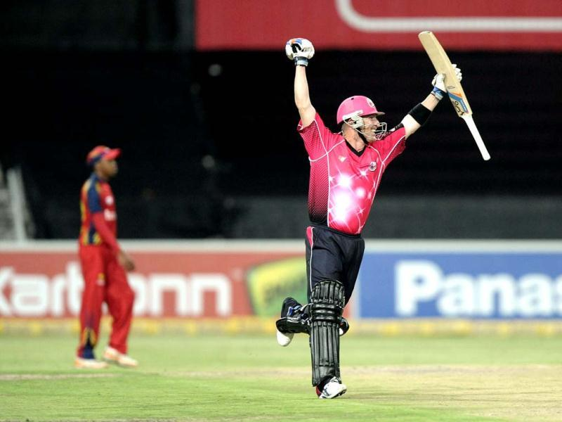 Sydney Sixers's captain Brad Haddin celebrates the victory of his team on during the final Champions League T20 (CLT20) match against the Highveld Lions at the Wanderers Stadium in Johannesburg. AFP Photo / Stephane De Sakutin