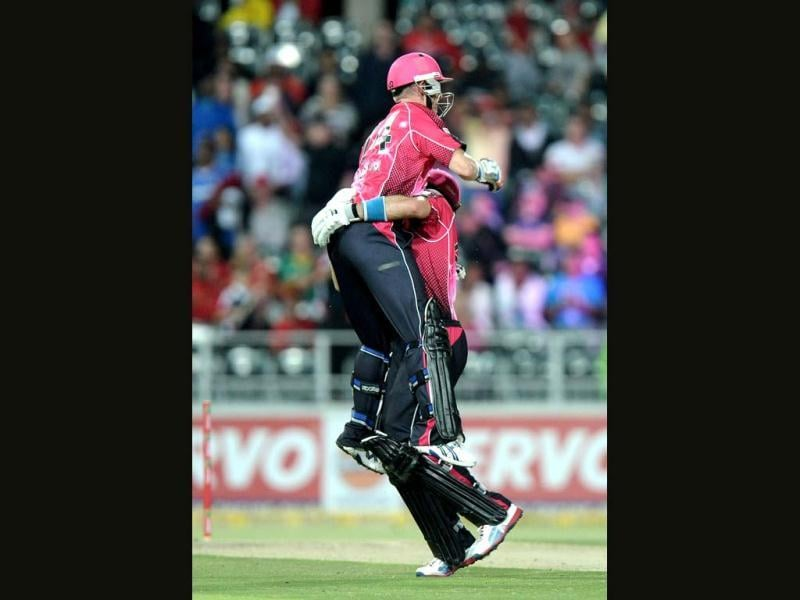 Sydney Sixers's captain Brad Haddin celebrates with his teammate Michael Lumb their victory on during the final Champions League T20 (CLT20) match against the Highveld Lions at the Wanderers Stadium in Johannesburg. AFP Photo / Stephane De Sakutin