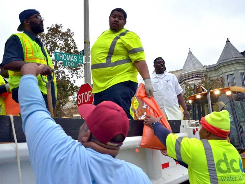 DC Water employee hand over bags of sand which were being distributed to residents by the local water-sewer authorities in downtown Washington ahead of Hurricane Sandy's landfall as flooding was expected throughout parts of the US capital. (AFP Photo)