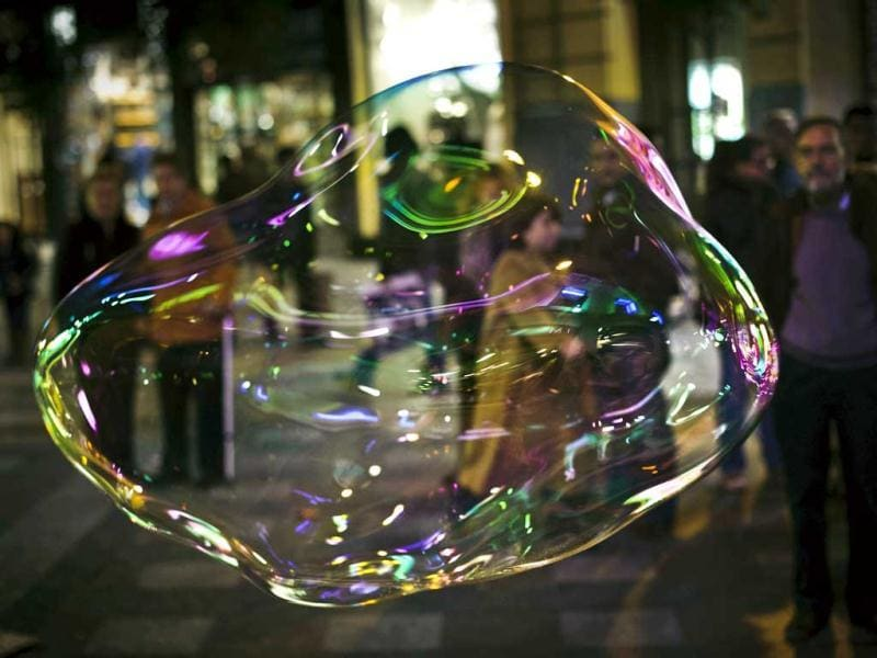 A soap bubble made by a man who performs for money in the street floats in Madrid. One Spaniard in four is now unemployed as the economic crisis tightens its grip. (AP Photo)