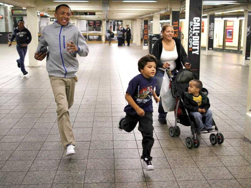A family runs for the last subway shuttle to Grand Central Station in New York in anticipation of Hurricane Sandy. Reuters