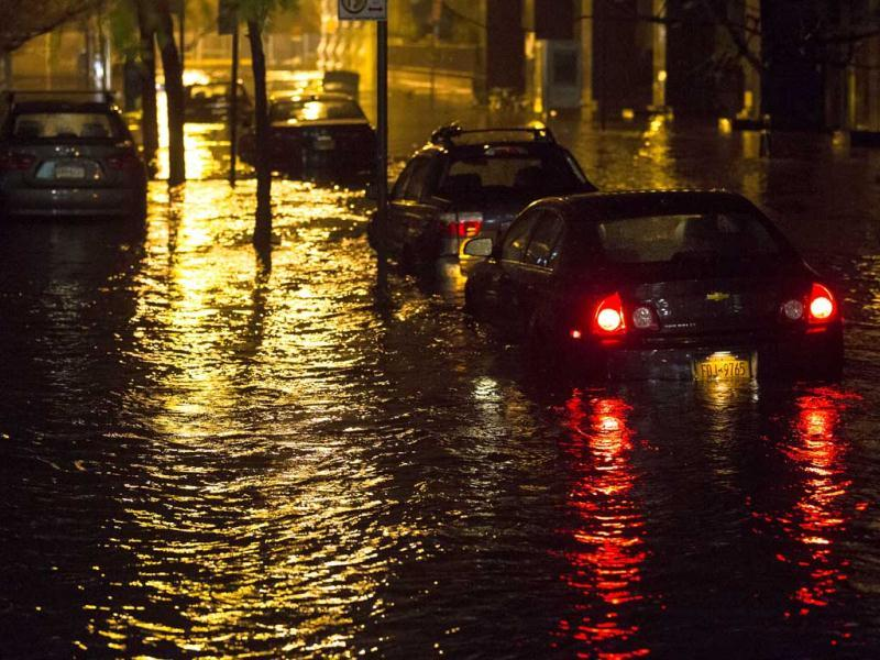Vehicles are submerged during a storm surge near the Brooklyn Battery Tunnel in New York. Superstorm Sandy zeroed in on New York's waterfront with fierce rain and winds that shuttered most of the nation's largest city, darkened the financial district and left a huge crane hanging off a luxury high-rise. AP photo