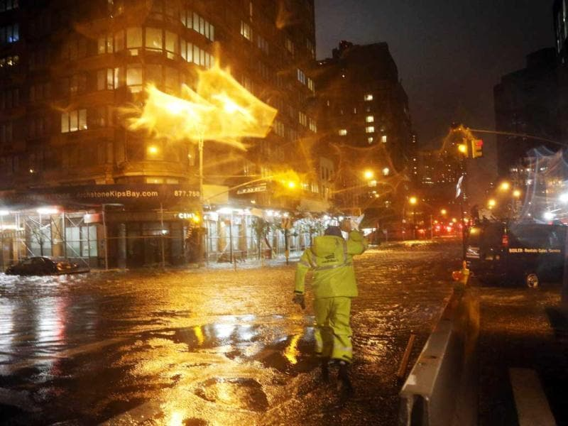 A Con Edison worker walks through the flood waters on the corner of 33th Street and 1st Street in front of NYU Langone Medical Center in Manhattan during rains from superstorm Sandy. AFP photo