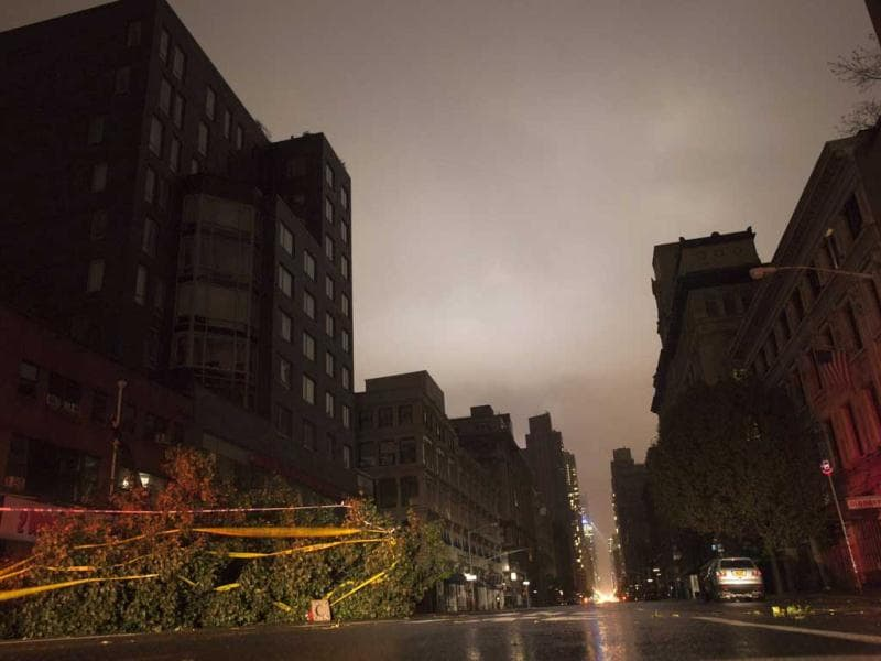 A fallen tree lays along a darkened Sixth Avenue in Chelsea during a blackout believed to be caused by rising river waters as superstorm Sandy made its approach in New York. Reuters photo