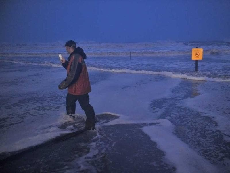 A man takes photographs as he walks through water on the beach near the time of high tide as superstorm Sandy approaches in Atlantic City, New Jersey. AFP photo