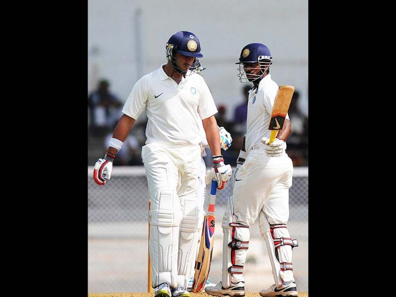 India A cricketer Yuvraj Singh (L) walks as teammate Abhinav Mukund raises his bat after scoring half a century during the first day of a three-day practice match between India A and England at the Cricket Club of India (CCI) grounds in Mumbai. AFP Photo/Pal Pillai