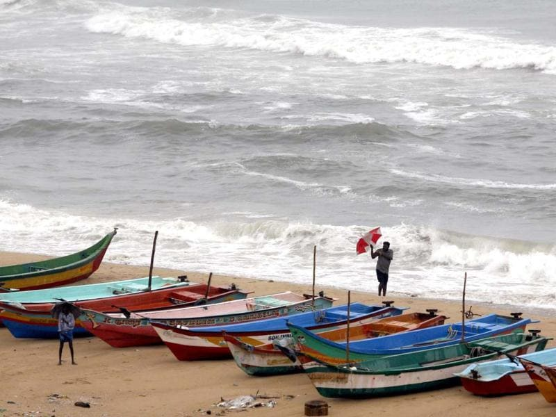 A man tries to hold on to his umbrella in strong winds, as he stands beside fishing boats on the Bay of Bengal coast as tidal waves approach the shore in Chennai. AP Photo